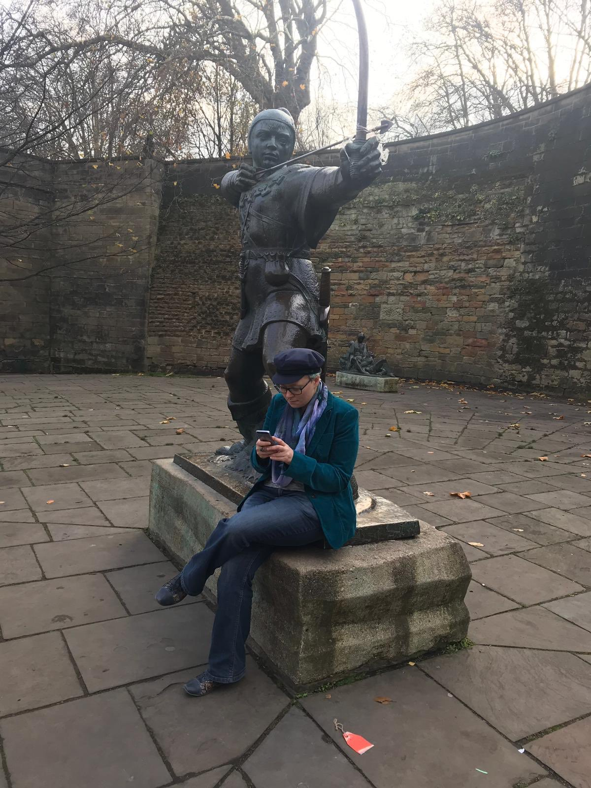 A person in a green jacket and blue hat sits on the pedestal of a statue of Robin Hood, writing on their phone.