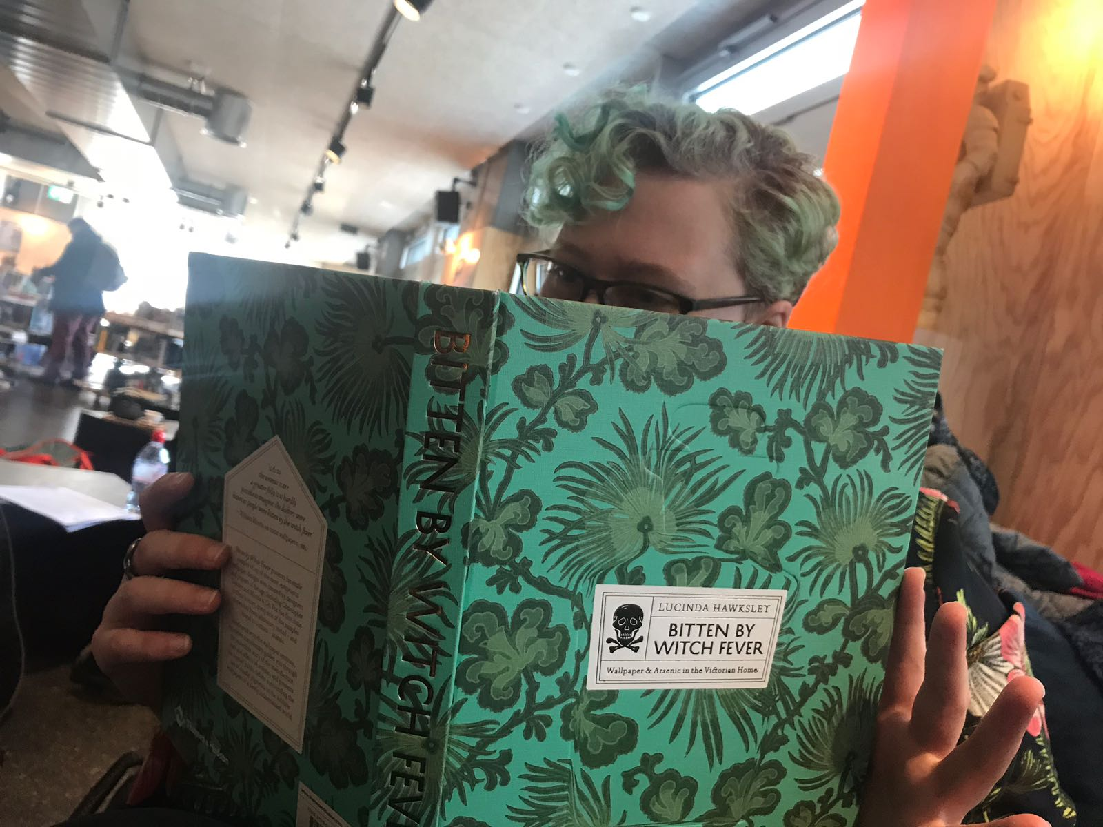 A person with curly green hair, reading a book with a green, flowery cover.